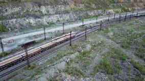 Den diesel- lokomotivet skjuter förrådsplats-bilen som fylls med spillrorstenen i bakgrunden av ett villebråd för att bryta för k arkivfilmer