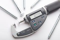 Den Digital mikrometern med justerbar tryckmätning med stål skruvar på vit bakgrund Arkivbild