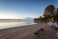 Den dimmiga morgonen i den provinsiella sjön av Algonquin parkerar, Ontario, Kanada med bänkar Arkivfoto