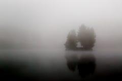 Den dimmiga mycket lilla ön på den dimmiga sjön i morgontimmar tänder Royaltyfria Bilder
