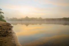 Den dimmiga soluppgången på floden Royaltyfri Fotografi