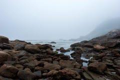 Den dimmiga stranden med vaggar och mist på skymning Arkivfoto