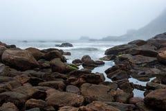 Den dimmiga stranden med vaggar och mist på skymning Arkivfoton