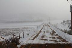 Den dimmiga vägen till ingenstans, snö täckte spår royaltyfri fotografi