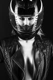 Den djärva flickamodellen i svart läderklänning, stil av vaggar på den nakna kroppen, mörk makeup och blöter hår med amotorcycleh Arkivbild