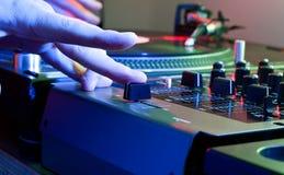 Den DJs handen tweaks korsfaderen av en musikblandare Royaltyfria Foton