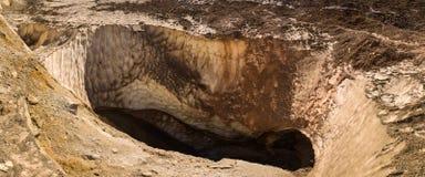 Den djupa gropen bildade i det 25m tjocka lagret av is i krater av den Mutnovsky vulkan Royaltyfri Bild