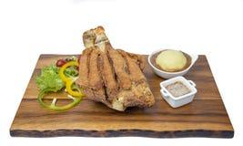 Den djupa stekte grisköttknogen tjänade som med den nya sallad och potatisen Arkivfoto