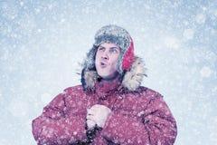 Den djupfrysta mannen i röd vinterkläder låter ångan ut ur hans mun, förkylning, snö, häftig snöstorm Arkivbild