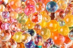 Den dominerande gula färgen av de runda hydrogelbollarna fördelade ut i kaotisk beställning Arkivfoto