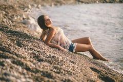 Den drömlika flickan kopplar av på stranden i modejeansskjortor Arkivfoto