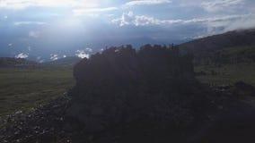 Den dramatiska sikten på ensamt vaggar på bergängar med solljusbakgrund Den flyg- sikten på enormt vaggar upptill av lager videofilmer