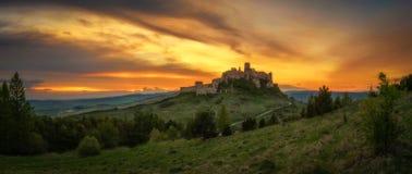 Den dramatiska solnedgången över fördärvar av den Spis slotten i Slovakien Arkivbild