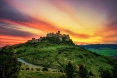 Den dramatiska solnedgången över fördärvar av den Spis slotten i Slovakien Royaltyfri Bild