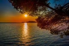 Den dramatiska solnedgången över havet och sörjer branchs arkivfoto