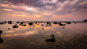 Den dramatiska solnedgången med reflekterar himmel i vattnet Royaltyfri Fotografi