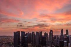 Den dramatiska solnedgången och lilan fördunklar över Singapore Arkivbild