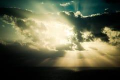 Den dramatiska solnedgången rays till och med en molnig mörk himmel över havet Arkivfoto