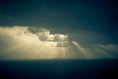 Den dramatiska solnedgången rays till och med en molnig mörk himmel över havet Royaltyfria Foton