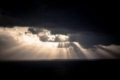 Den dramatiska solnedgången rays till och med en molnig mörk himmel över havet Arkivbild