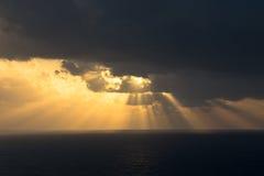 Den dramatiska solnedgången rays till och med en molnig mörk himmel över havet Arkivbilder