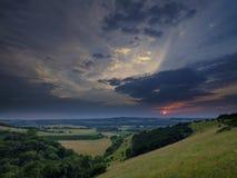 Den dramatiska sommarsolnedgången över Beacon Hill från den nära gamla Winchester kullen på söderna besegrar, nära Warnford i den fotografering för bildbyråer