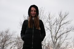 Den dramatiska ståenden av en ledsen ung kvinna i en vinter parkerar Royaltyfria Bilder
