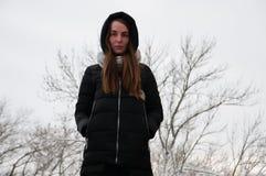 Den dramatiska ståenden av en ledsen ung kvinna i en vinter parkerar Royaltyfri Bild