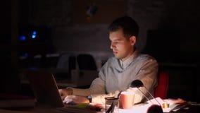 Den driftiga moderna caucasian affärsmannen skriver på tangentbordet av hans bärbar dator, medan sitta inomhus mörk bakgrund, sen lager videofilmer