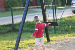 Den driftiga pojken tömmer gunga Fotografering för Bildbyråer