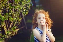 Den drömlika lilla flickan parkerar på våren, Arkivbild