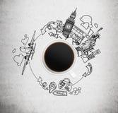 Den drog bästa sikten av en kaffekopp och skissar av London och New York på den konkreta bakgrunden Arkivfoton