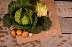 Den drog kål, blomkålen, broccoli och handen undertecknar ecoprodukten på svart Royaltyfria Foton