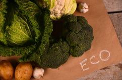 Den drog kål, blomkålen, broccoli och handen undertecknar ecoprodukten på svart Royaltyfria Bilder