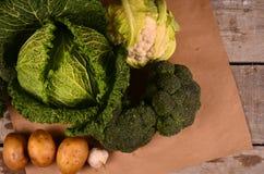 Den drog kål, blomkålen, broccoli och handen undertecknar ecoprodukten på svart Arkivbilder