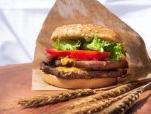 Den dubbla hamburgaren woodden på brädet arkivbild