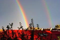 Den dubbla regnbågen över taklägger Royaltyfri Foto