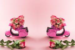 Den Duble buketten av rosor blommar i korg p? backseaten av den gulliga rosa sparkcykeln och den stora rosen p? rosa bakgrund fotografering för bildbyråer