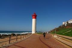 Den Durban strandpromenaden längs den Indiska oceanen- och Umhlanga fyren i Umhlanga vaggar Arkivfoto