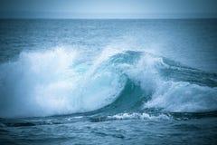 Den dyka upp vågen av havet nära kusten Arkivfoto