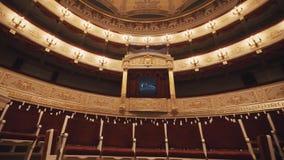 Den dyra balkongen i konserthall, vakanta stolar ror, röda draipings