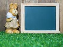 Den easter kaninen står bredvid svart tavla Svart tavla med easter kanin som förläggas på grönt gräs Påskdagbegrepp Kopia Spac Arkivbild