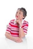 Den eftertänksamma äldre damen ler - äldre kvinna som isoleras på vitbaksida Arkivbild