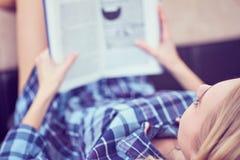 Den eftertänksamma flickan är läseboken Ung gullig kvinna som hemma studerar och att ligga på soffan Arkivfoto