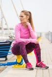 Den eftertänksamma flickan i sportar bär att vila efter övningen i hamnstad, sund aktiv livsstil Royaltyfria Bilder