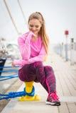 Den eftertänksamma flickan i sportar bär att vila efter övningen i hamnstad, sund aktiv livsstil Arkivfoton