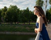 Den eftertänksamma flickan ser in i avståndet nära floden Arkivfoto