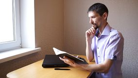 Den eftertänksamma grabben läser notepaden lager videofilmer