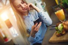 Den eftertänksamma kvinnan med en telefon i hans hand sitter på tabellen i modernt kafé, fokusen placeras på en smartphone på tab Arkivfoton