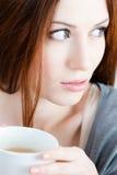 Den eftertänksamma kvinnan med kuper av tea arkivfoton